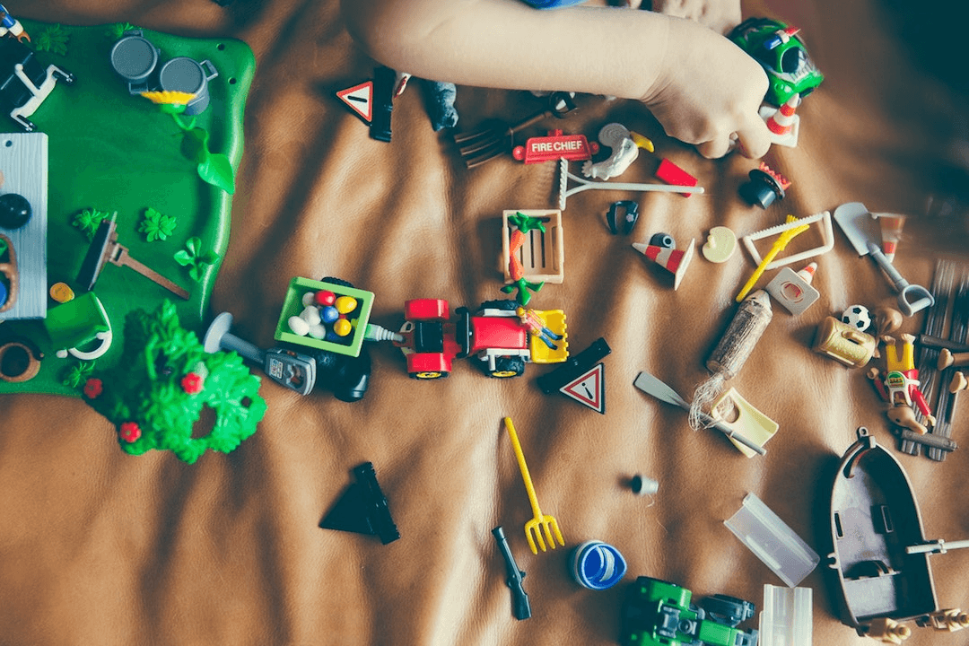 A child playing with broken toys on a brown sheet