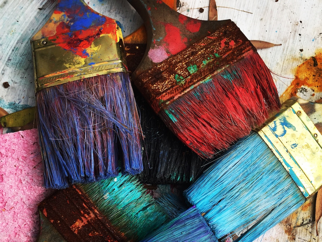 A pile of colorful, dirty paintbrushes