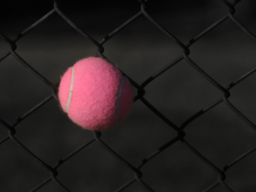 A pink tennis ball stuck in a chainlink fence
