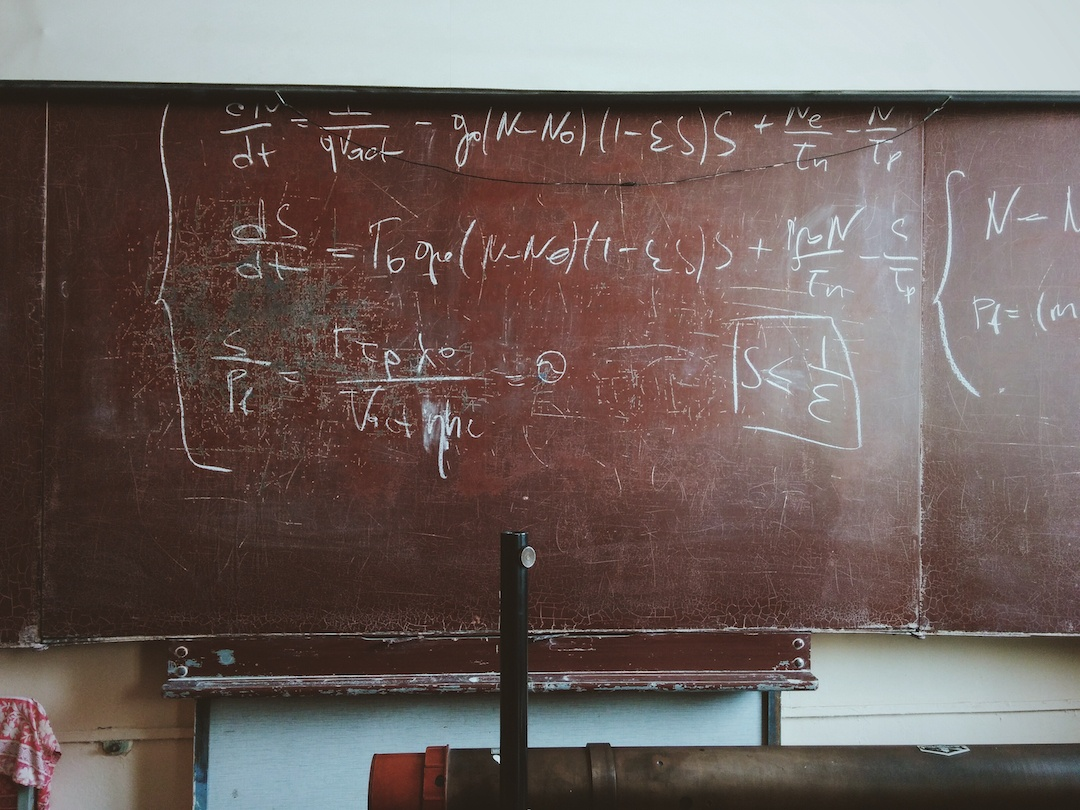 Complicated equations written on a chalk board